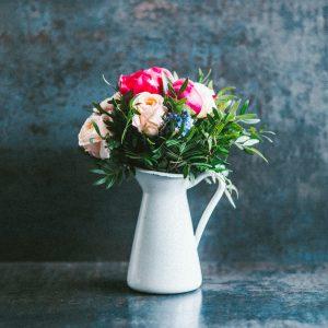 red and white roses in white ceramic vase