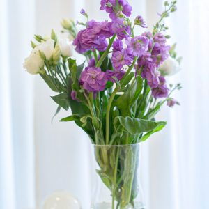 purple and white flowers in clear glass vase